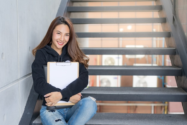 Young student female sit on stairs  with the folder and copy-book in campus area