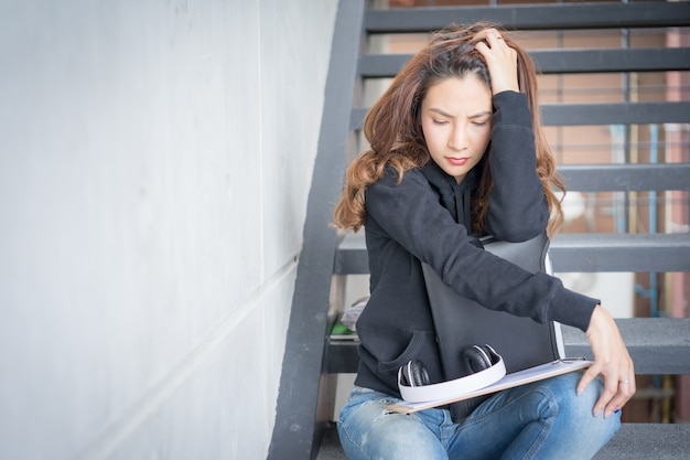 Young student female strictly sit on stairs  with the folder and copy-book in campus area