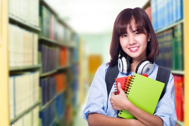 어린 학생은 검색을 위한 교과서를 찾고 도서관에서 지식을 배웁니다.