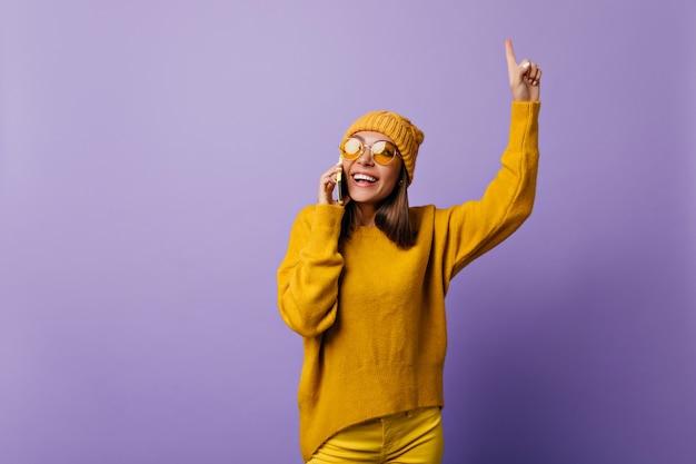 Молодой студент породил новую идею, разговаривая по телефону. радостная своему открытию, девушка в желтой одежде вдохновила позировать на сиреневом фоне.