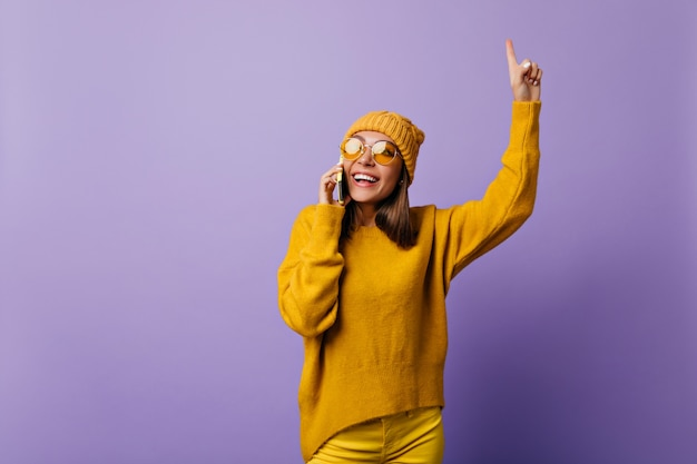 Il giovane studente ha generato una nuova idea parlando al telefono. gioiosa per la sua scoperta, la ragazza in abiti gialli ha ispirato la posa sul lilla