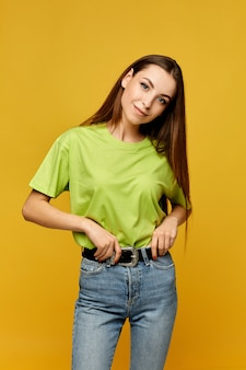 Young student girl in a blank yellow t-shirt and jeans posing at the yellow wall, isolated