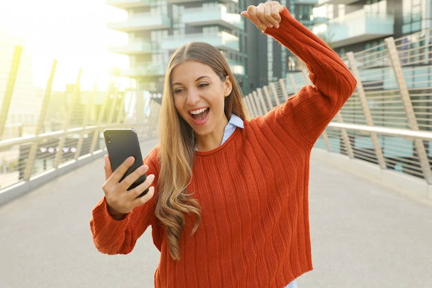 Young student girl celebrating good news on her mobile phone cheering