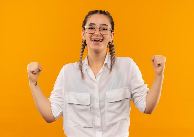 Ragazza giovane studente in bicchieri con le trecce in camicia bianca stringendo i pugni felici ed entusiasti che si rallegrano del suo successo in piedi sopra la parete arancione