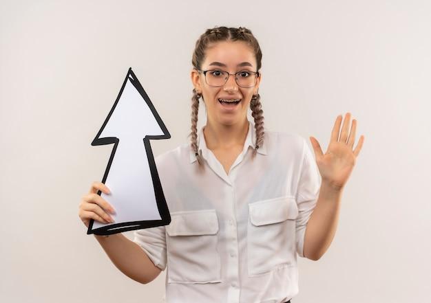 Ragazza giovane studente in bicchieri con le trecce in camicia bianca tenendo la freccia alzando la mano nella resa in piedi sul muro bianco