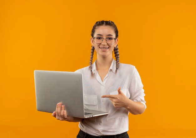 Young student girl in glasses with pigtails in white shirt holding laptop pointing with finger to it smiling confident standing over orange wall