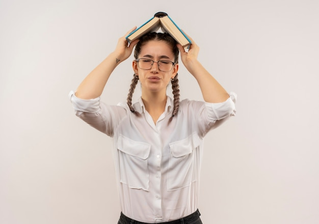 Young student girl in glasses with pigtails in white shirt holding open book over her head looking disappointed standing over white wall
