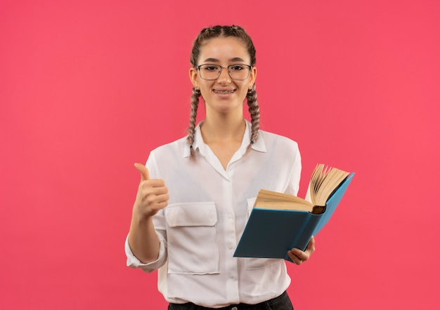 Giovane ragazza dell'allievo in vetri con le trecce in camicia bianca che tiene libro aperto che guarda al fronte sorridente che mostra i pollici in su in piedi sopra la parete rosa