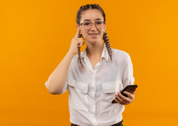 Young student girl in glasses with pigtails in white shirt holding smartphone pointing with finger to temple smiling standing over orange wall