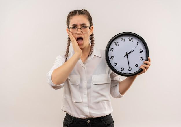 Ragazza giovane studente in bicchieri con le trecce in camicia bianca che tiene l'orologio da parete guardando in avanti confuso e molto ansioso in piedi sopra il muro bianco