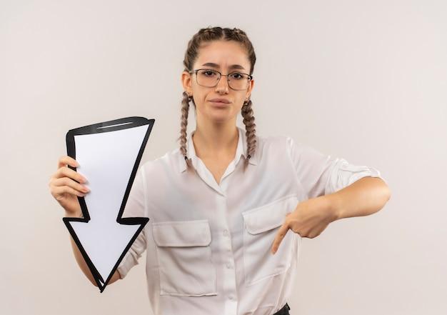 Ragazza giovane studente in bicchieri con le trecce in camicia bianca che tiene la freccia bianca che punta con il dito verso il basso che sembra scontento in piedi sopra il muro bianco