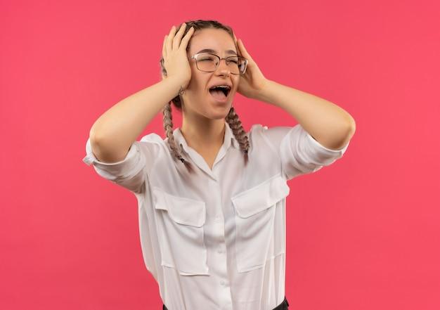 Ragazza giovane studente in bicchieri con le trecce in camicia bianca che guarda da parte tenendo la testa con le mani gridando in preda al panico in piedi sopra il muro rosa