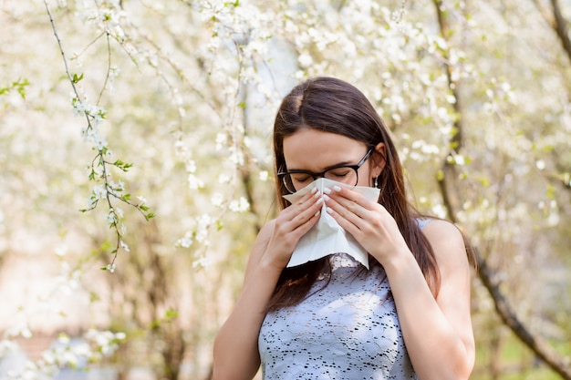 くしゃみをしながら白いハンカチで顔を隠して若い学生の女の子
