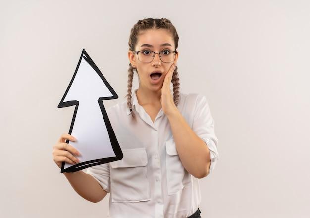 흰색 벽 위에 서 놀란 정면을 찾고 화살표를 들고 흰 셔츠에 땋은 안경에 젊은 학생 소녀