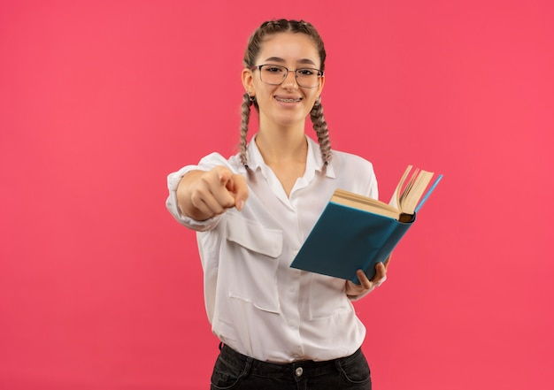 ピンクの壁の上に立って笑顔の正面に指で指している本を保持している白いシャツのピグテールとメガネの若い学生の女の子