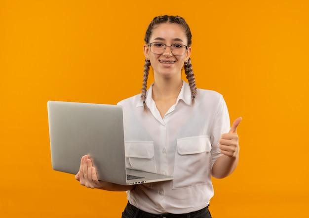 Молодая студентка в очках с косичками в белой рубашке держит ноутбук, глядя вперед, улыбаясь, показывает палец вверх, стоя над оранжевой стеной