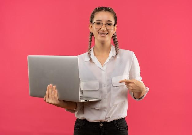 Молодая студентка в очках с косичками в белой рубашке держит ноутбук, указывая пальцем на него, уверенно улыбаясь, стоя над розовой стеной