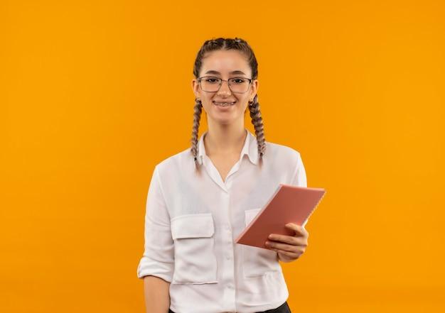 오렌지 벽 위에 서 자신감 미소로 앞을 찾고 노트북을 들고 흰 셔츠에 땋은 안경에 젊은 학생 소녀