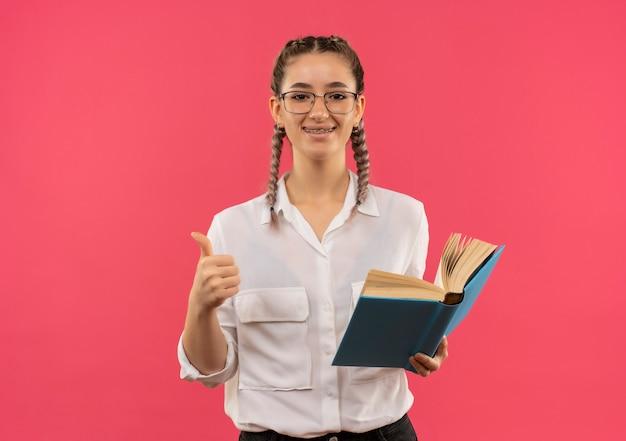 Молодая студентка в очках с косичками в белой рубашке держит открытую книгу, глядя вперед, улыбаясь, показывает палец вверх, стоя над розовой стеной