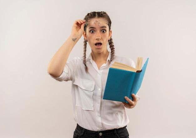 開いた本を持って正面を向いて眼鏡を外して白い壁の上に立って驚いて立っている白いシャツのピグテールと眼鏡をかけた若い学生の女の子