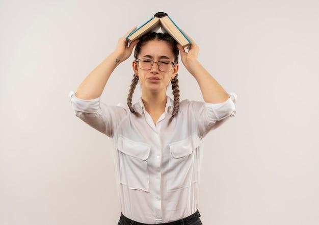 白い壁の上に立ってがっかりしているように見える彼女の頭の上に開いた本を保持している白いシャツのピグテールとメガネの若い学生の女の子