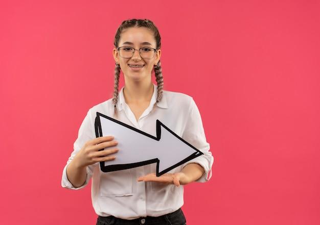분홍색 벽 위에 유쾌하게 서 웃고 전면을 찾고 흰색 화살표를 들고 흰 셔츠에 땋은 안경에 젊은 학생 소녀