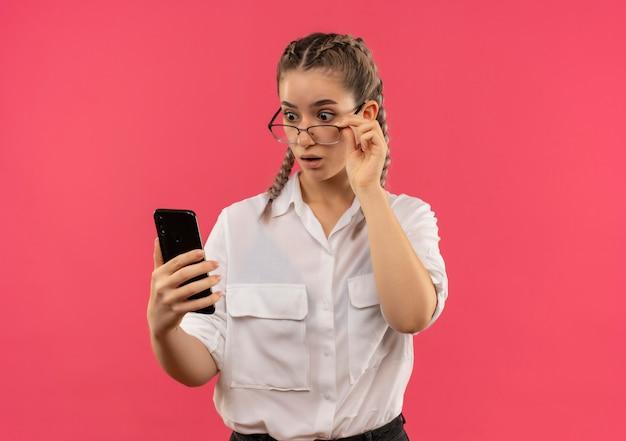 ピンクの壁の上に立っている彼女の携帯電話の画面を見て驚いて驚いた白いシャツのピグテールとメガネの若い学生の女の子