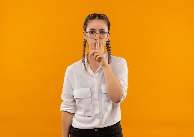 オレンジ色の壁の上に立っている唇に指で沈黙のジェスチャーを作る正面を見て白いシャツのピグテールとメガネの若い学生の女の子