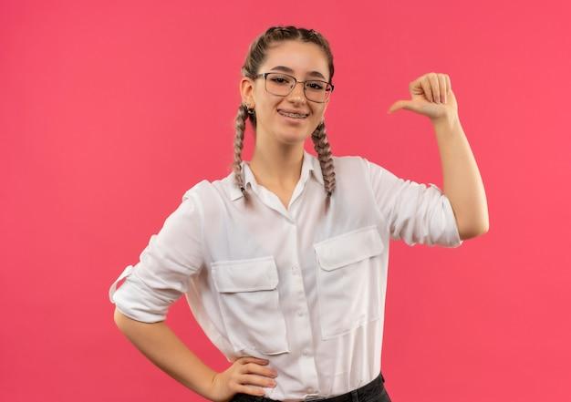 Молодая студентка в очках с косичками в белой рубашке смотрит вперед, улыбается счастливая и позитивная, указывая на себя, стоящую над розовой стеной