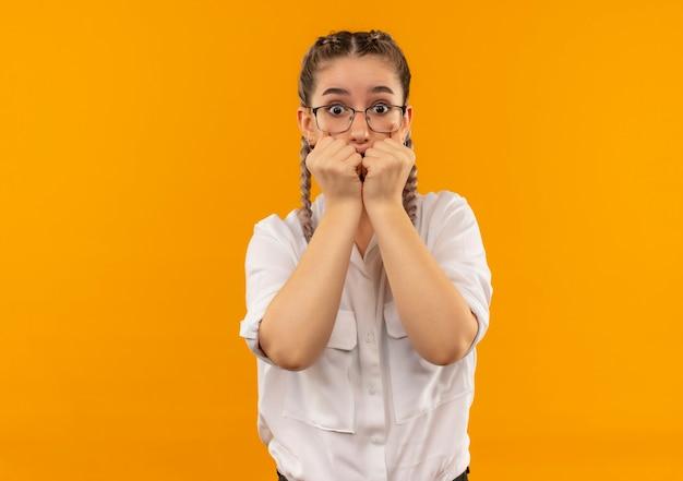 オレンジ色の壁の上に立っているストレスと心配の噛む爪を正面に見て白いシャツのピグテールとメガネの若い学生の女の子