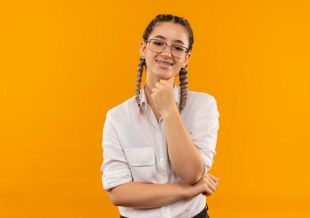 오렌지 벽 위에 서있는 자신감 미소로 정면을 찾고 흰 셔츠에 땋은 안경에 젊은 학생 소녀