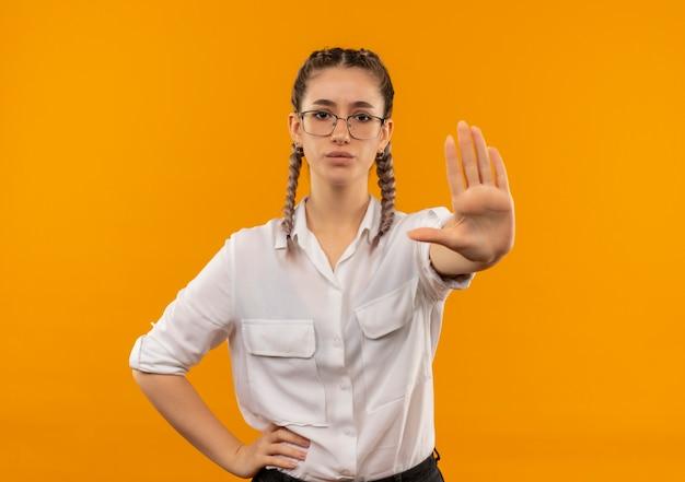 Молодая студентка в очках с косичками в белой рубашке делает знак остановки с рукой, смотрящей вперед, с серьезным лицом, стоящим над оранжевой стеной
