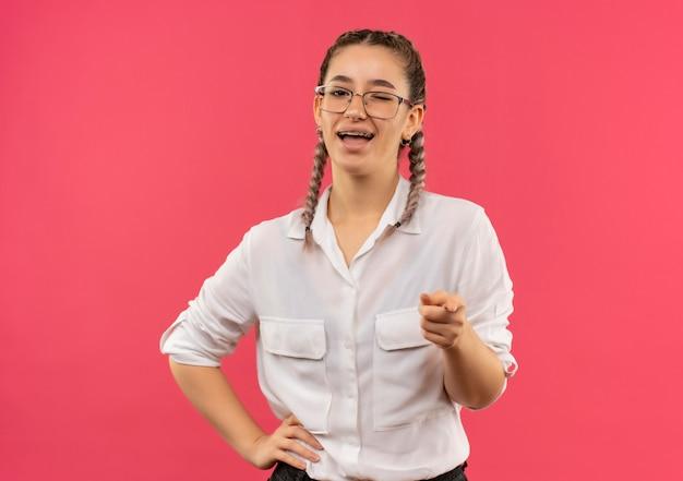 Молодая студентка в очках с косичками в белой рубашке, указывая указательным пальцем вперед, широко улыбается и позитивно стоит над розовой стеной