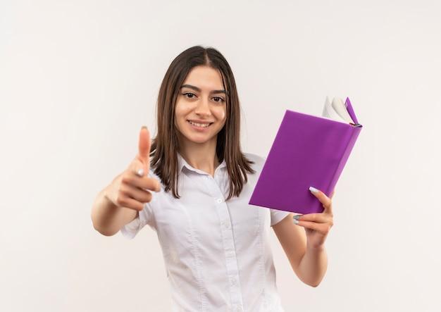 Молодая студентка в белой рубашке держит открытую книгу, показывая пальцы вверх, улыбаясь, стоя над белой стеной
