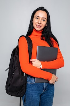 Young student girl isolated on gray wall, smiling at camera, pressing laptop to chest, wearing backpack, ready to go to studies, start new project and suggest new ideas.