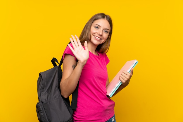 Young student girl over isolated yellow saluting with hand with happy expression