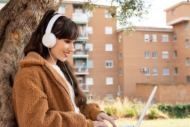 공원에서 그녀의 노트북으로 화상 회의를 만드는 젊은 학생 소녀.