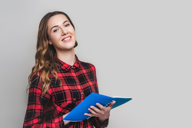 A young student girl in a plaid shirt holds a notebook on a grey wall with  for text. cute student with documents papers in the hands. girl learning english.