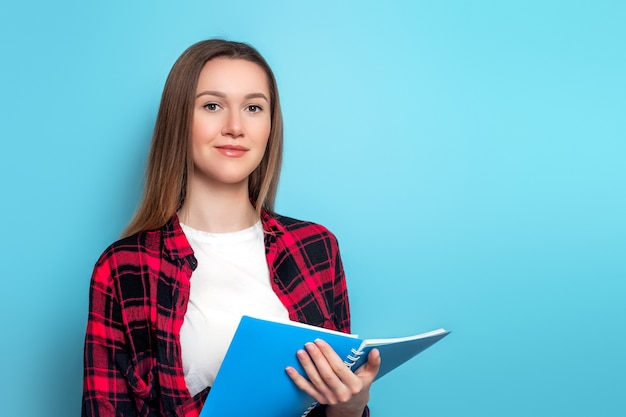 A young student girl in a plaid shirt and a white t-shirt holds a notebook on a blue wall . cute student with documents papers in the hands. student girl conducting a survey testing