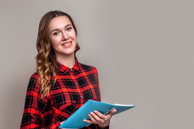 A young student girl in a plaid shirt with wavy hair holds a notebook on a grey wall . student girl conducting a survey testing.