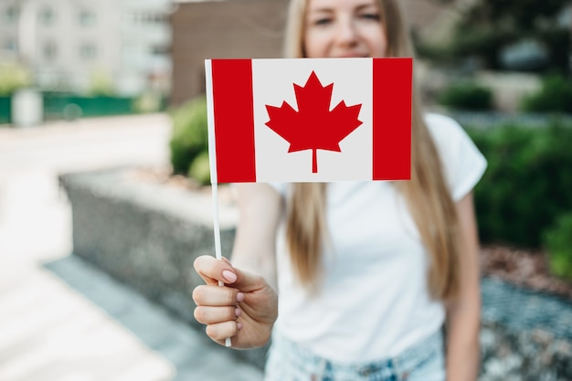 Young student girl shows a small canadian flag and stands against the background of the university