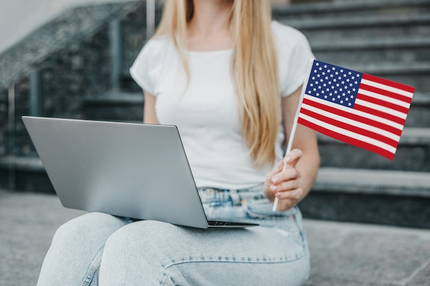 Young student girl sits on stairs, shows a small american flag on the background of the university. close up