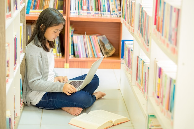 Young student girl sitting  in a library