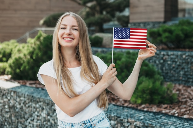 Young student girl smiling and shows a small american flag and stands against the background of the university