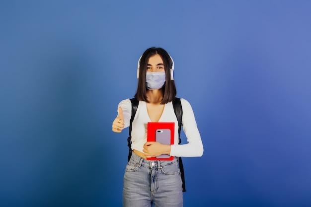 若い学生の女の子は、医療用マスクを着用し、カメラを見て、ジェスチャーをクールに示しています。