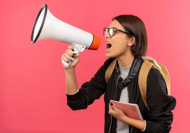ピンクの背景に分離されたスピーカーで話しているメモ帳を保持している縦断ビューで立っている眼鏡とバックバッグを身に着けている若い学生の女の子