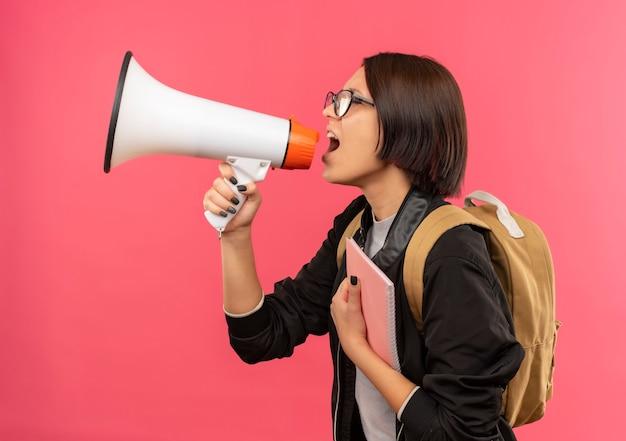 Молодая студентка в очках и задней сумке, стоящая в профиле, держит блокнот, разговаривает спикером, изолированным на розовом