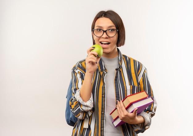 Ragazza giovane studente con gli occhiali e borsa posteriore che tengono i libri e si prepara a mordere la mela isolata su priorità bassa bianca con lo spazio della copia