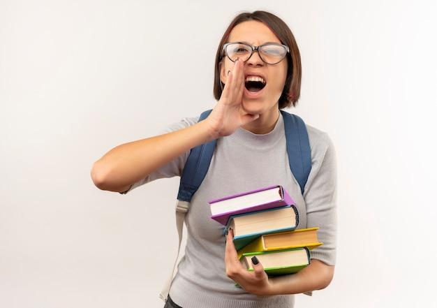 Ragazza giovane studente con gli occhiali e borsa posteriore in possesso di libri mettendo la mano vicino alla bocca chiamando qualcuno isolato su sfondo bianco
