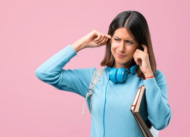 Young student girl with blue sweater and headphones covering both ears. back to school